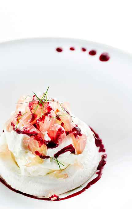 Pomelo pavlova with Chantilly cream, cassis coulis & candied kaffir lime leaves